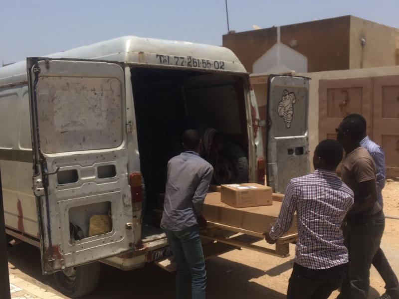 Männer ziehen Karton aus dem Lastwagen